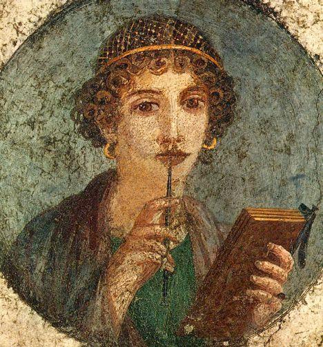 Mujer de la antigua roma tomando una tabla de cera con la mano izquierda y un lápiz con la mano derecha, que apoya en su boca con un gesto pensativo.