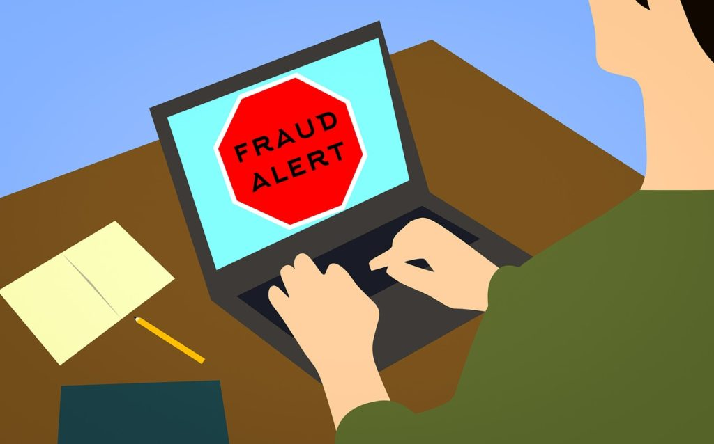 "hombre usando una laptop cuya pantalla dice ""fraud alert"""